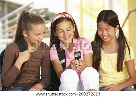 Pre teen girls in school with cellphone - stock photo