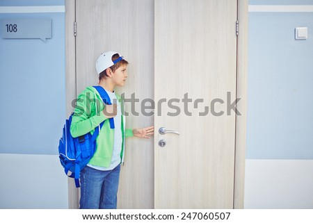 Pre-teen schoolboy opening classroom door and looking inside - stock photo