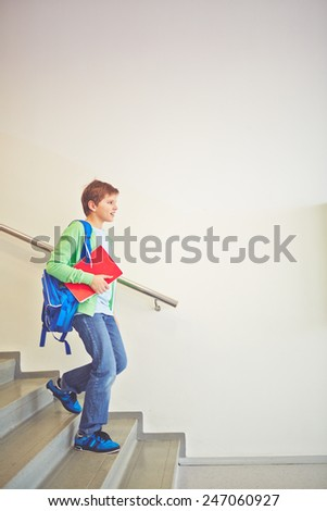 Pre-teen schoolboy with backpack going downstairs - stock photo