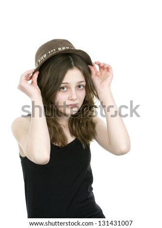 Pre teen young girl putting on a hat on white background - stock photo