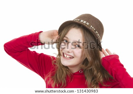Pre teen young girl smiling and putting on her hat on white background - stock photo