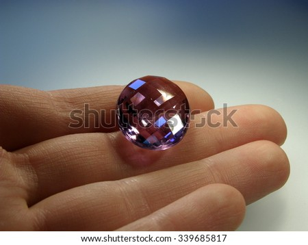 Precious gemstone amethyst faceted in hand - stock photo