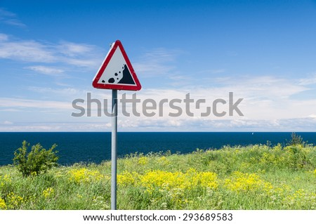 Precipice edge warning sign. Danger sea cliff hidden by grass and flowers - stock photo