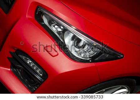 Predatory car headlight and hood of powerful sports car with matte red paint and wheel with silver disc  - stock photo