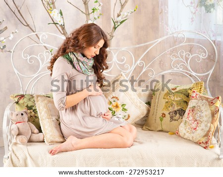 pregnancy, mother in a sunlit room - stock photo