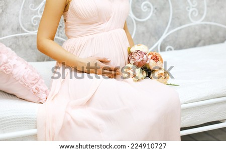 Pregnancy, motherhood and happy future mother concept - pregnant woman and bouquet flowers sitting on the bed - stock photo