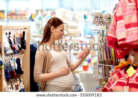 pregnancy, people, sale and expectation concept - happy pregnant woman shopping at children clothing store - stock photo
