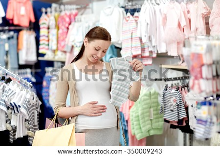 pregnancy, people, sale and expectation concept - happy pregnant woman with shopping bag buying baby bodysuit at children clothing store - stock photo