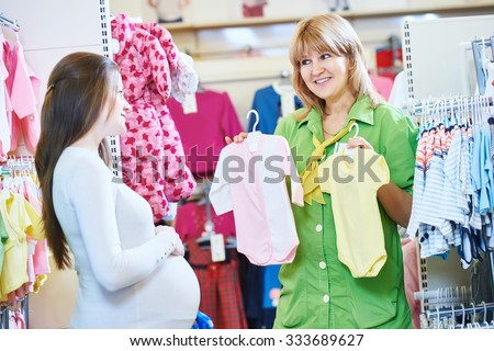 Pregnancy shopping. Female saleswoman selling newborn clothes to young pregnant woman at baby shop store - stock photo