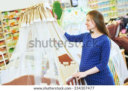 Pregnancy shopping. Pregnant woman choosing cradle cot or crib for newborn at baby shop store - stock photo