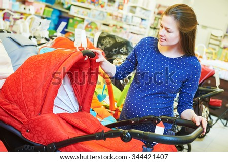 Pregnancy shopping. Pregnant woman choosing pram for newborn carriage at baby shop store - stock photo