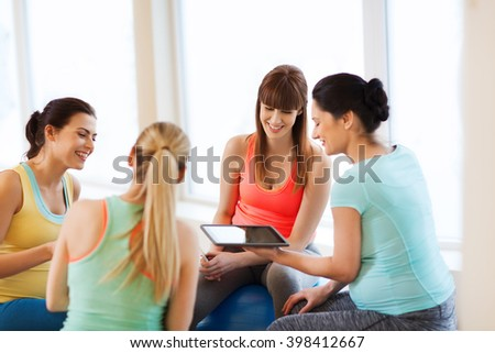 pregnancy, sport, fitness, people and healthy lifestyle concept - group of happy pregnant women with tablet pc computer and smartphone sitting on balls in gym - stock photo