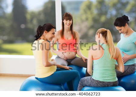 pregnancy, sport, fitness, people and healthy lifestyle concept - group of happy pregnant women sitting and talking on balls in gym - stock photo