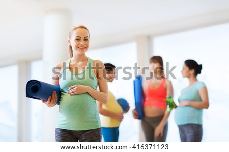 pregnancy, sport, fitness, people and healthy lifestyle concept - happy pregnant woman with mat in gym - stock photo