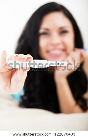 pregnancy test good result not pregnant smiling woman, young girl happy smile in bedroom, focus on foreground one stripe - stock photo