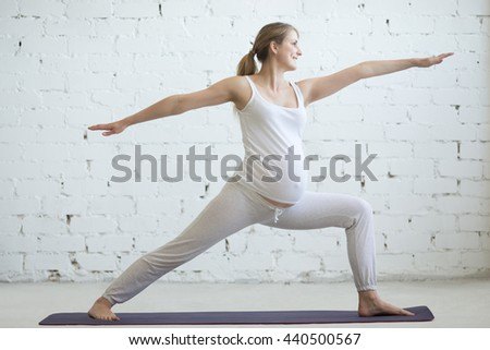Pregnancy Yoga and Fitness concept. Portrait of beautiful young pregnant yoga model working out indoor. Pregnant happy fitness person enjoying yoga practice at home. Prenatal Warrior II posture - stock photo