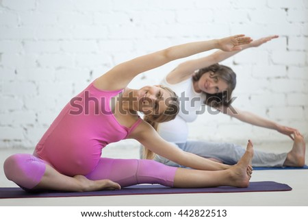 Pregnancy Yoga and Fitness concept. Portrait of two attractive young pregnant yoga models working out indoor. Pregnant fitness women practicing yoga in class. Prenatal Janu Sirsasana pose. Full length - stock photo