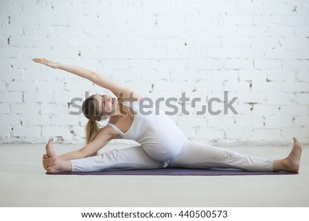 Pregnancy Yoga and Fitness concept. Portrait of young pregnant yoga model working out indoors. Pregnant smiling fitness person practicing yoga at home. Prenatal side bend in seated splits - stock photo