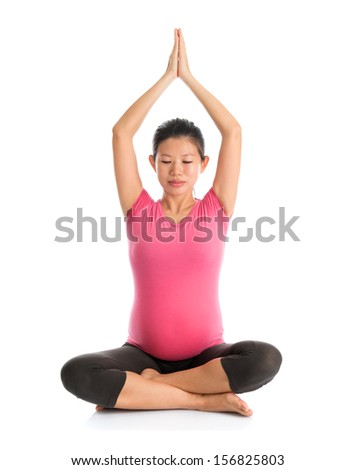 Pregnancy yoga class. Full length healthy Asian pregnant woman doing yoga exercise stretching, full body isolated on white background. Yoga positions lotus arms stretch. - stock photo