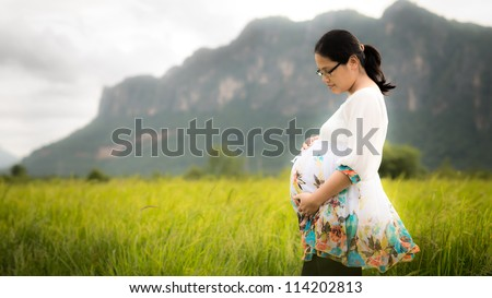 pregnant Asian woman wearing floral white dress affectionately holding her belly outside with newly planted rice field, mountains, and cloudy sky in background. - stock photo