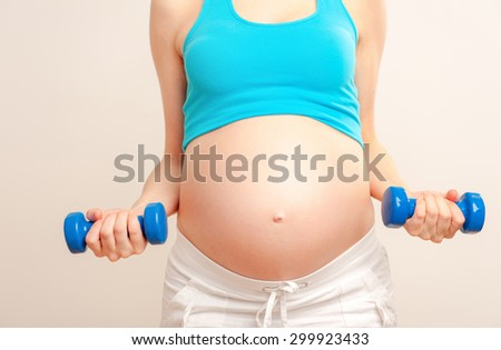 Pregnant female do exercise against white background , body part, lifting dumbbells, active and sportive pregnancy, healthy motherhood concept - stock photo