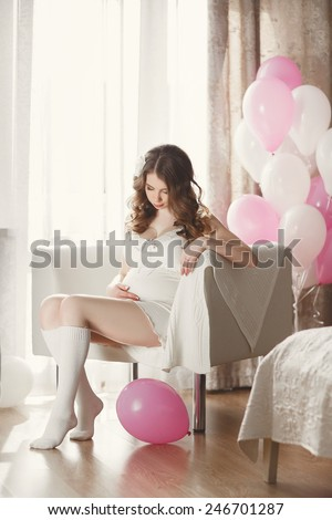 Pregnant Happy smiling Woman sitting on a sofa and caressing her belly. Mom Expecting Baby. Pregnant Woman Belly. Pregnancy. Beautiful Pregnant Woman. Maternity concept. Baby Shower - stock photo