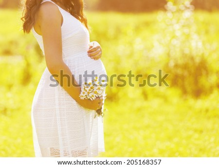 Pregnant lovely woman in white dress with wildflowers in summer sunny day, tender moment, warm sunlight - stock photo