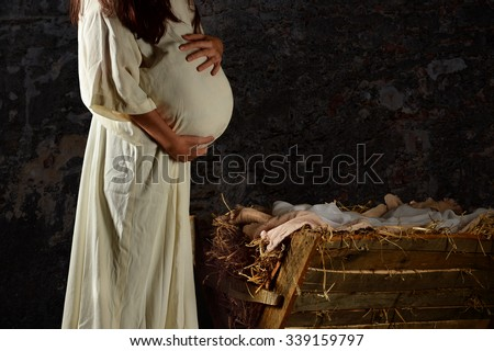 Pregnant Mary holding stomach in front of Manger - stock photo