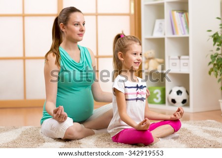 Pregnant mother and child daughter do yoga, relax in lotus position on fit mat at home - stock photo