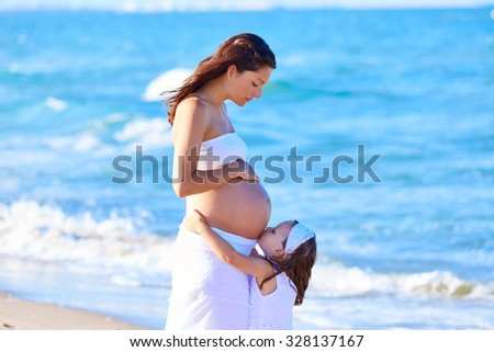 Pregnant mother and daughter on the beach together kissing belly - stock photo