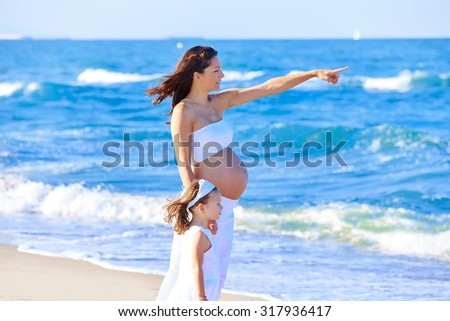 Pregnant mother and daughter on the beach together pointing finger - stock photo