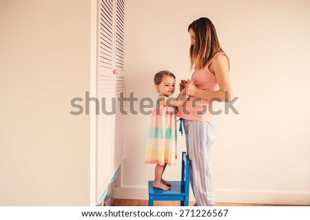 pregnant mother and her baby daughter are happy together at home - stock photo