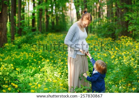 Pregnant mother and her son having fun outdoors in the woods - stock photo