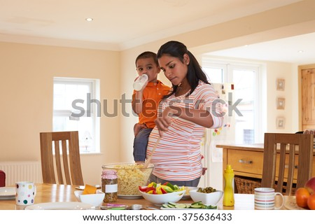 Pregnant Mother Carrying Son Whilst Making Salad In Kitchen - stock photo