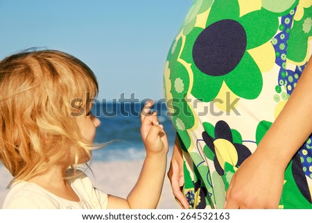 Pregnant mother with her daughter playing on the beach - stock photo