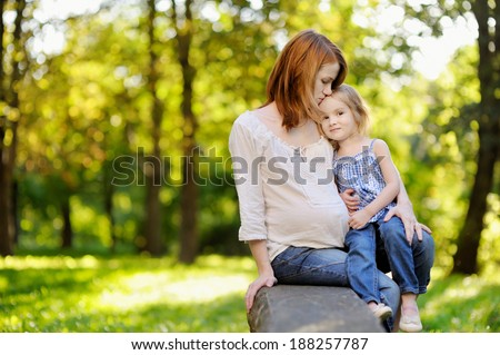 Pregnant mother with her small daughter outdoors - stock photo