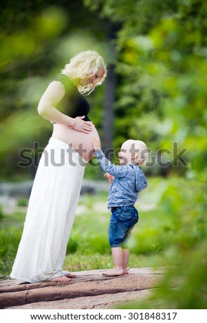 Pregnant mother with her son - stock photo