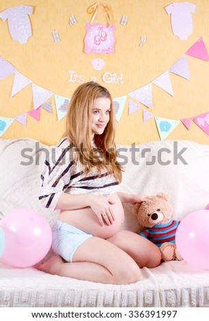 Pregnant smiling woman sitting on a sofa and caressing her belly. - stock photo