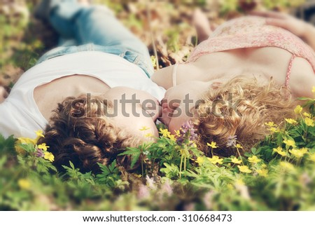 Pregnant wife and her husband lying on green grass - stock photo