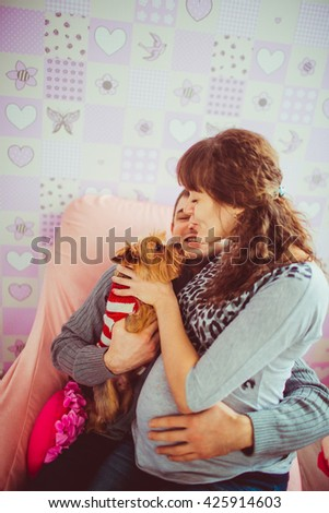 Pregnant wife is trying to kiss her dog - stock photo