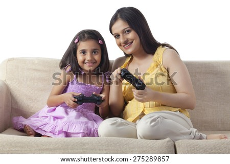 Pregnant woman and her daughter playing video game - stock photo