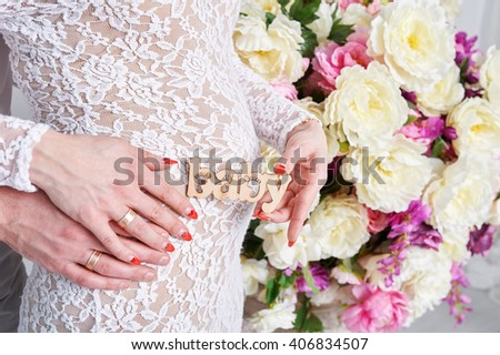 Pregnant Woman and Her Husband holding hands in a heart shape - stock photo