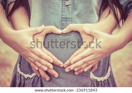 Pregnant Woman and Her Husband holding her hands in a heart shape on her baby bump. - stock photo