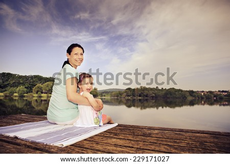 pregnant woman and her little daughter making yoga exercise at a lake. Lichtenfels, Germany - stock photo