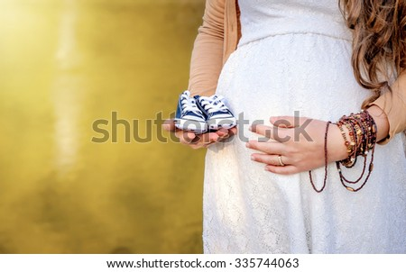 Pregnant woman belly holding baby booties. Healthy pregnancy. Newborn baby booties in parents hands. Pregnant woman belly - stock photo