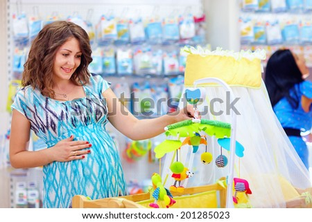 pregnant woman buying cradle with mobile toy for baby - stock photo