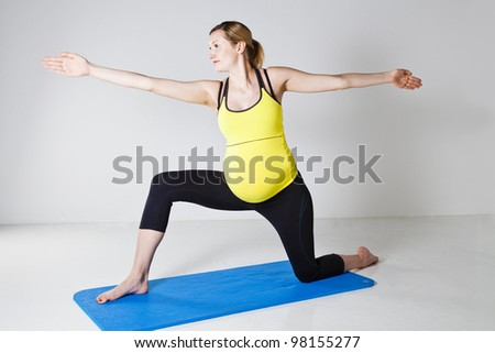 Pregnant woman doing a yoga stretching and balance exercise on a mat - stock photo