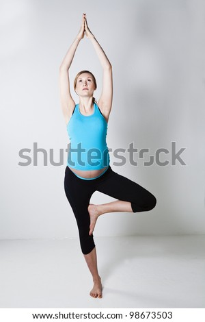 Pregnant woman doing a yoga stretching and balance exercise with arms above head - stock photo