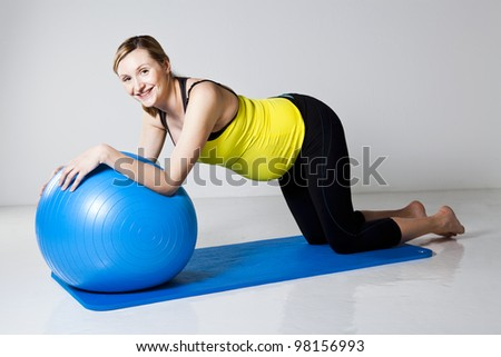 Pregnant woman doing an abdominal core strengthening exercise using a fitness ball on a mat - stock photo