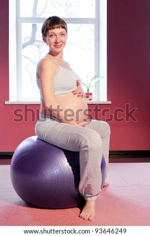Pregnant woman doing exercise - stock photo